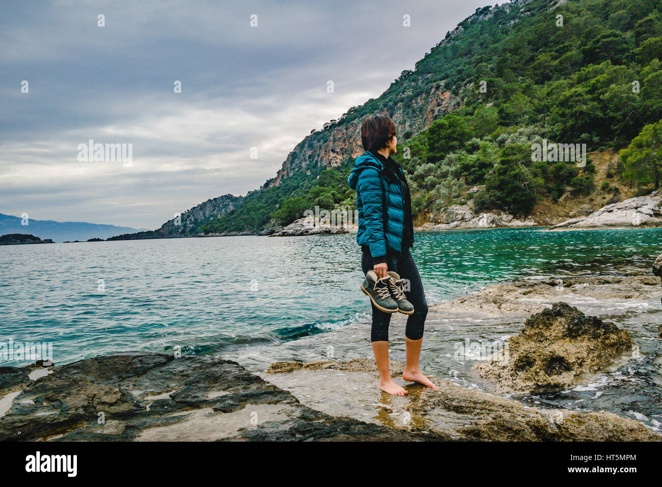 attractive fashion model girl standing on the wet rock barefoot, holding hiking boots side view - Stock Image