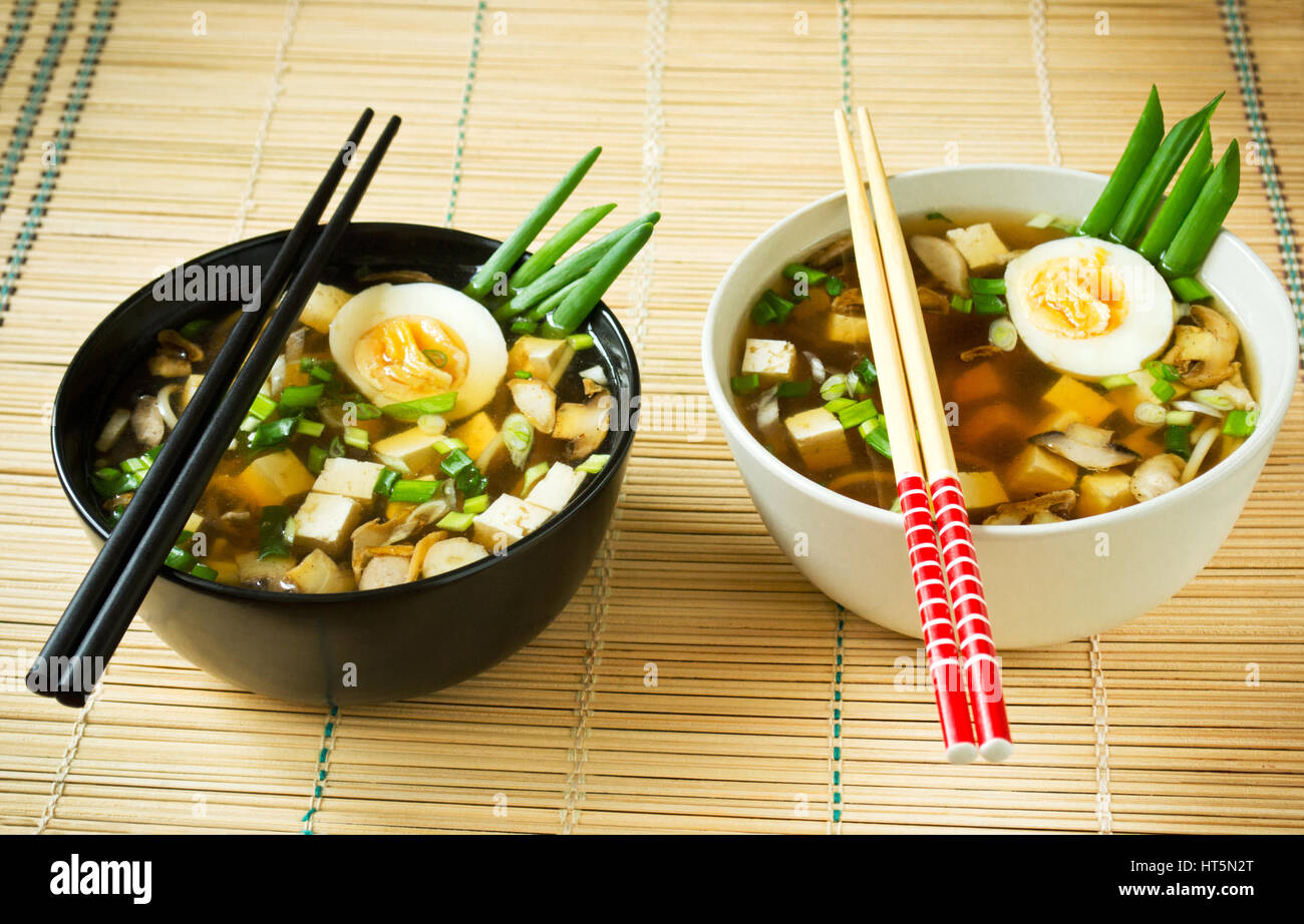 Miso soup in bowls on bamboo mat - Stock Image