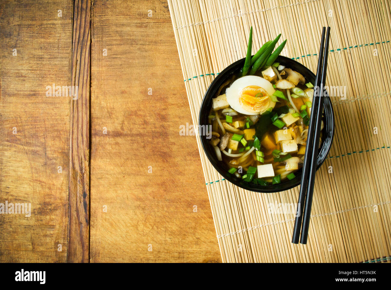 Japanese miso soup in black cup on bamboo mat background - Stock Image