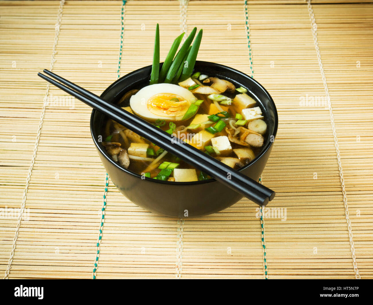 Japanese miso soup in black bowl on bamboo mat - Stock Image