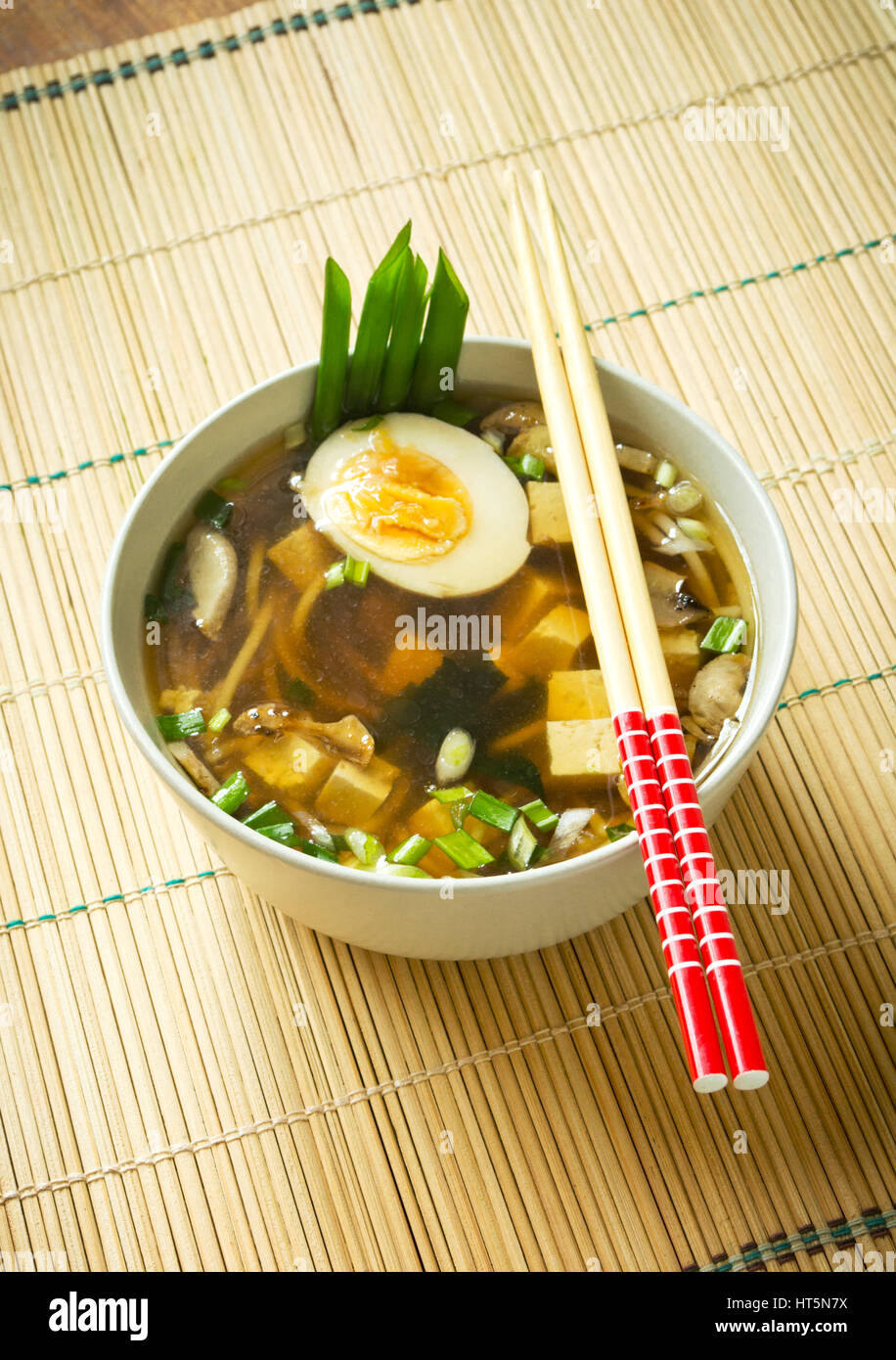 Miso soup in white bowl on bamboo mat - Stock Image