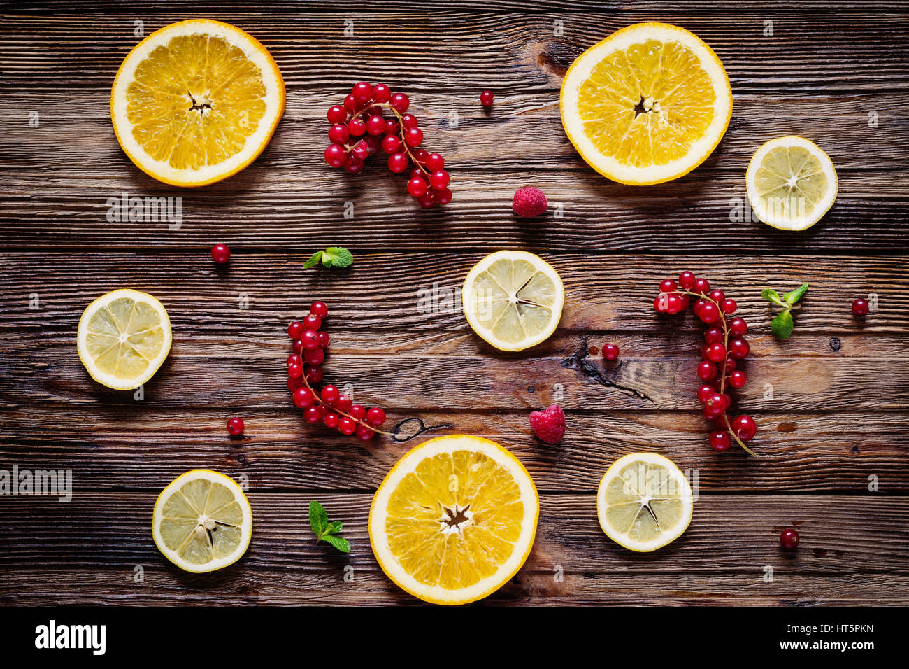 Lemon and orange rings, red currants, raspberries and mint leaves on wooden background. Table top view. Fresh fruit Stock Photo