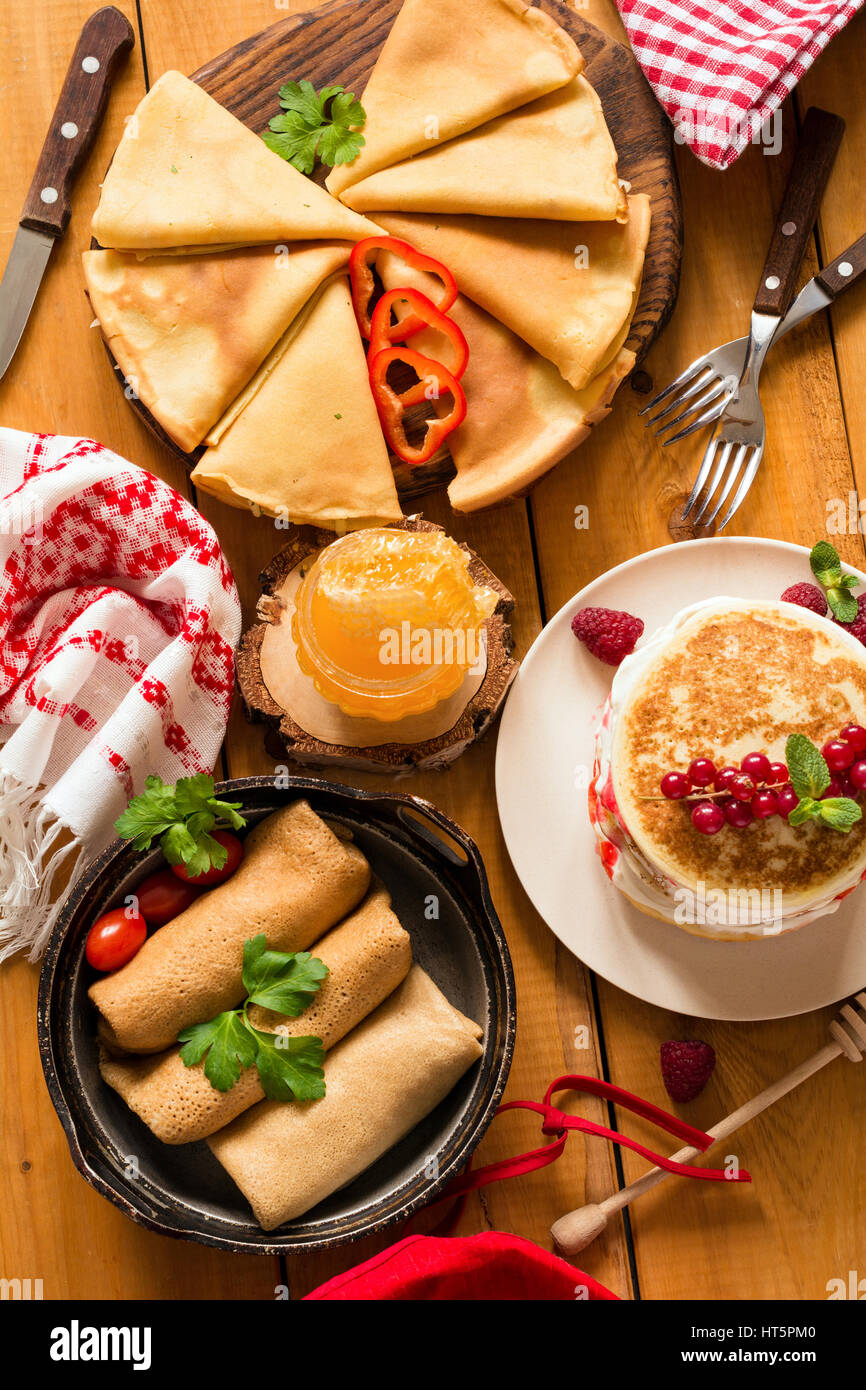 Various types of crepes and pancakes on rustic wooden table, top view - Stock Image