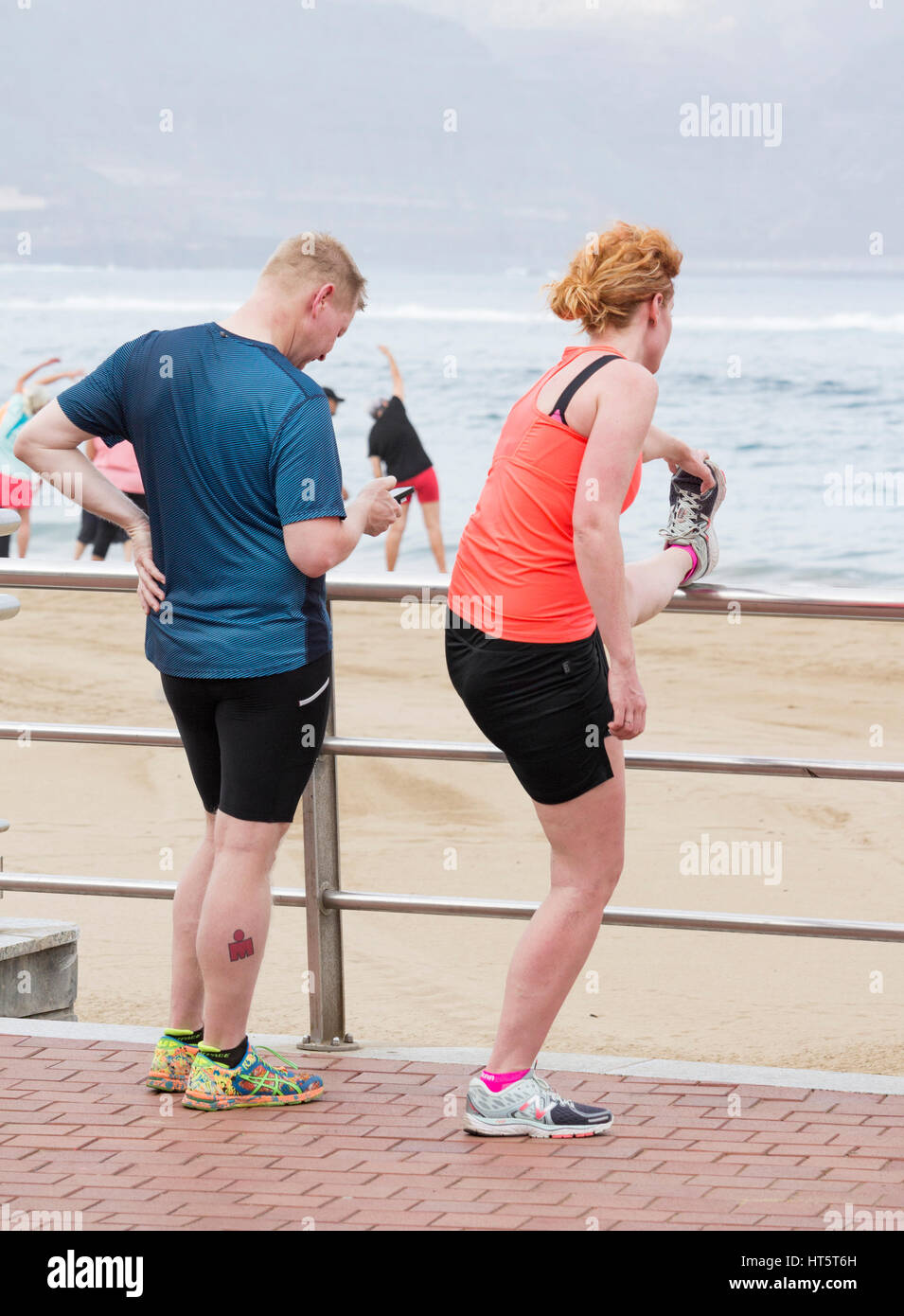 Joggers stretching overlooking beach. Man looking at mobile phone screen Stock Photo
