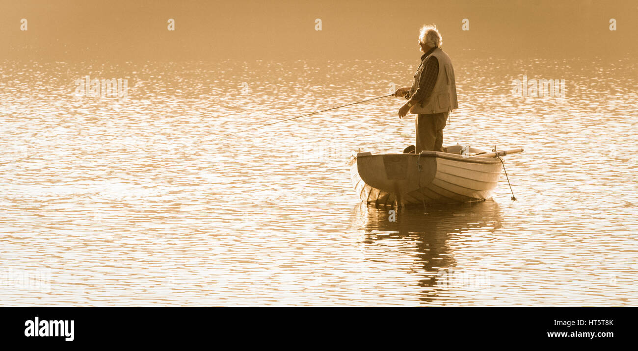 Mature man fly fishing from boat on Lockwood Beck, North York Moors National Park, North Yorkshire, England, UK. - Stock Image