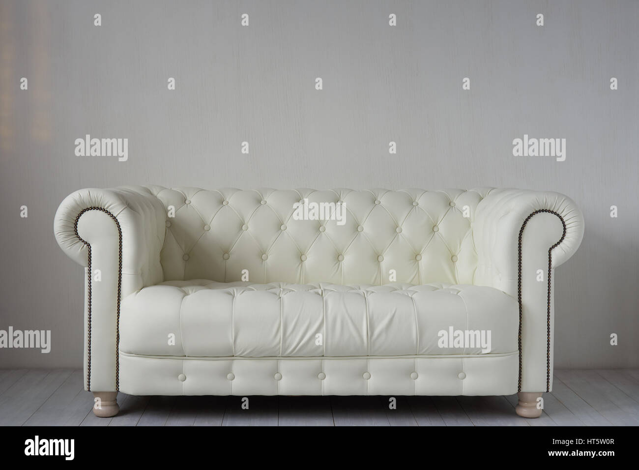 White leather sofa on white wooden floor near white textured wall ...