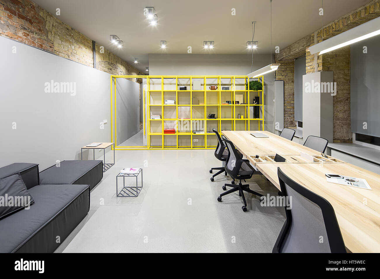 Loft Style Office With Gray And Brick Walls. There Are Glowing Lamps, Dark  Sofa With Pillow, Wooden Tables With Chairs, Small Metal Tables, Metal Yell