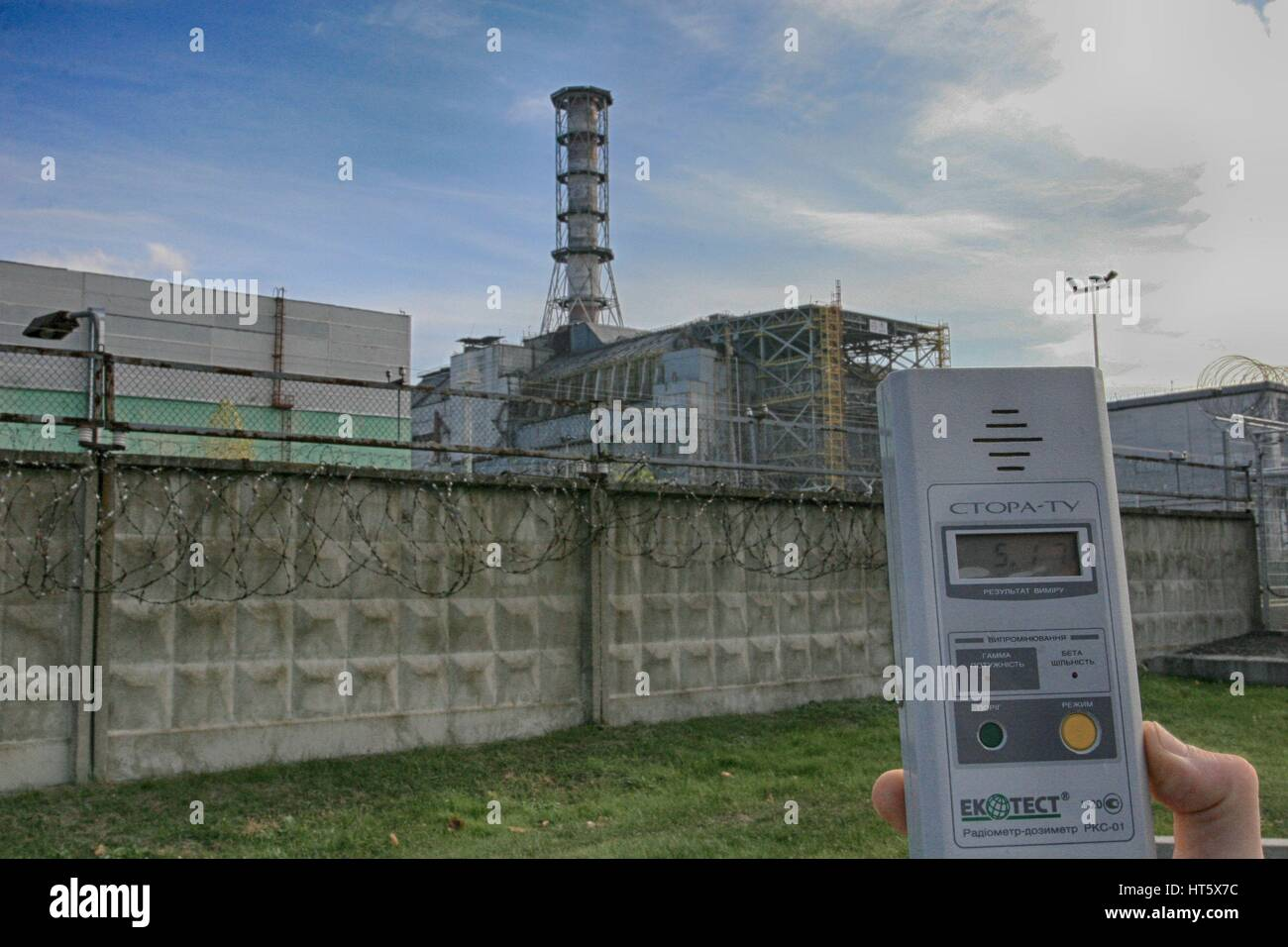 Dosimeter showing high radioactivity at Chernobyl nuclear power station with exploded reactor 4 in the background - Stock Image