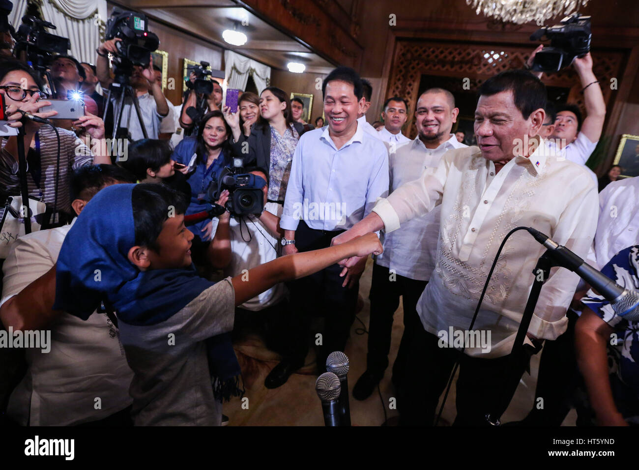 Philippine President Rodrigo Duterte jokes with kidnap victim Rexon Romoc after being reunited with his parents - Stock Image