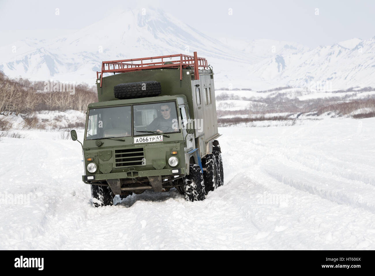 Old Swedish military off-road vehicle Volvo Laplander C304 (six-wheel drive) khaki color, driving in snow along - Stock Image