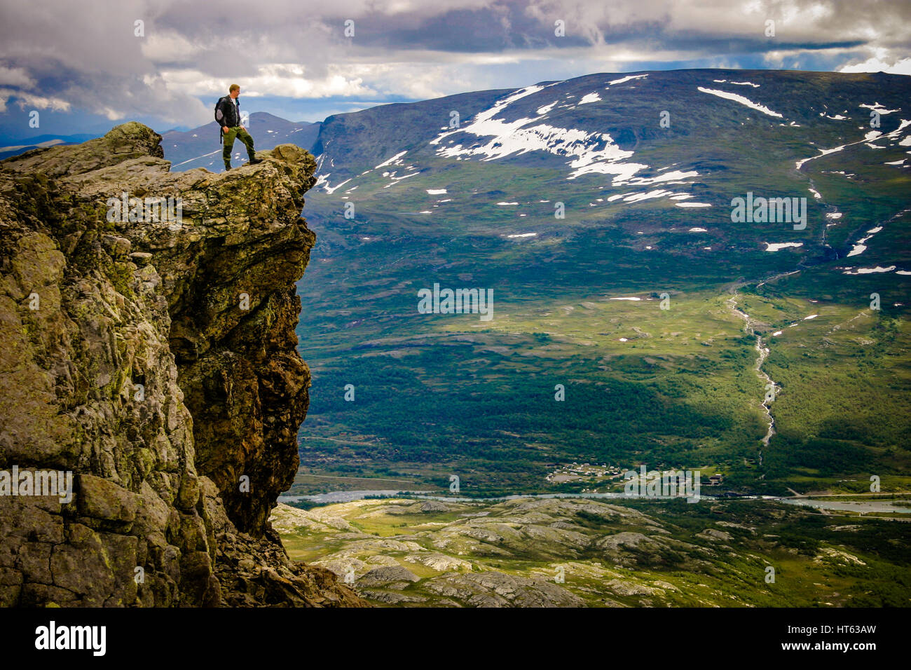 Man standing at edge of cliff at Mount Besseggen, Norway Stock Photo