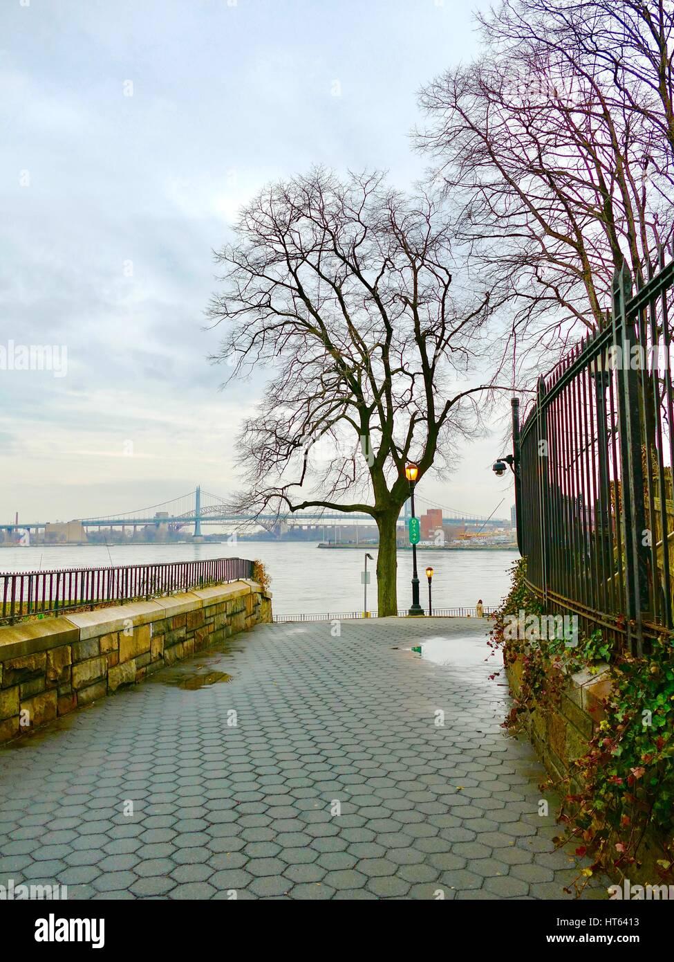 Looking across the East River towards the RFK bridge on a gray, rainy day. New York City, New York, USA - Stock Image