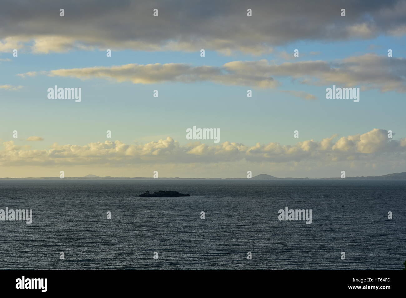 Dark steel-like gray sea with small almost black rock just above water surface under bright sky with some dark cloudy - Stock Image