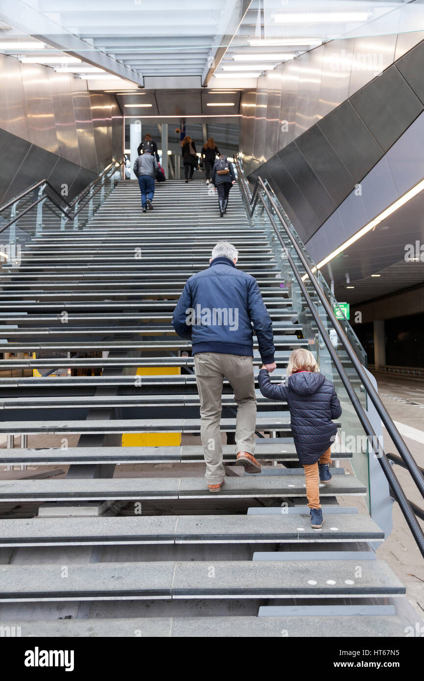 older man and small girl climb stairs to terminal of utrecht central railway station in holland Stock Photo