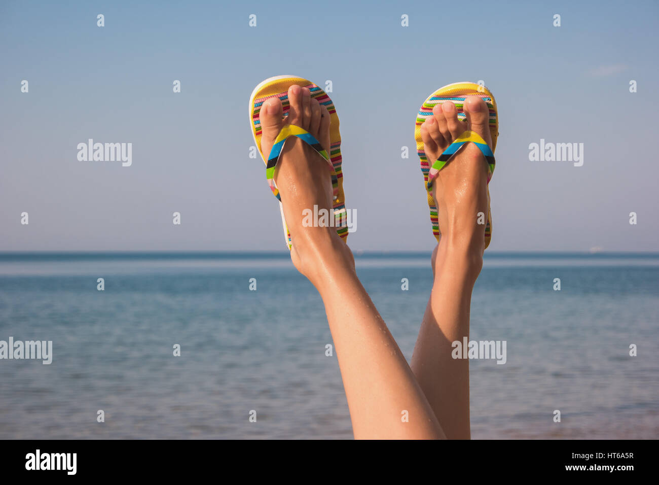 3629bbb78 Female legs and sea. Feet in colorful flip flops. Away from bustle ...