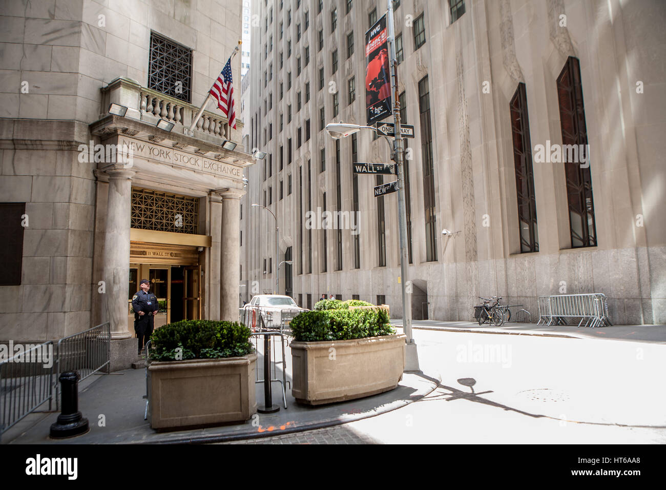 """A guard is standing on the entrance of the New York Stock Exchange. It is also known as the """"Big Board"""" is an American - Stock Image"""
