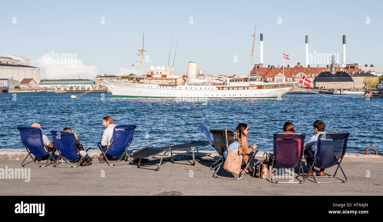 Local people from Copenhagen relax at lunchtime by the waterfront at Toldboden in Copenhagen. In the background - Stock Image