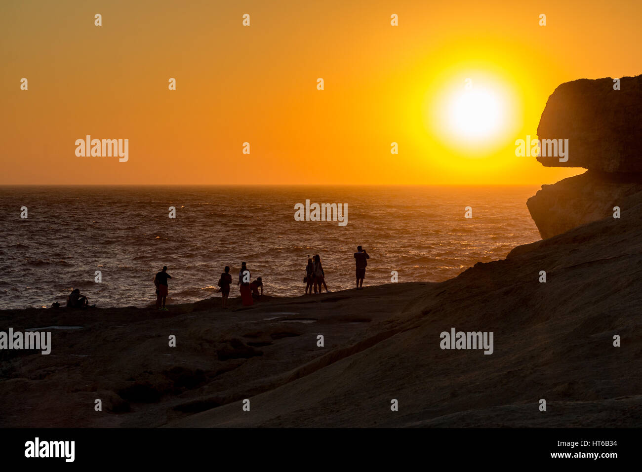 Silhouettes of people by the Azure Window, Malta - Stock Image