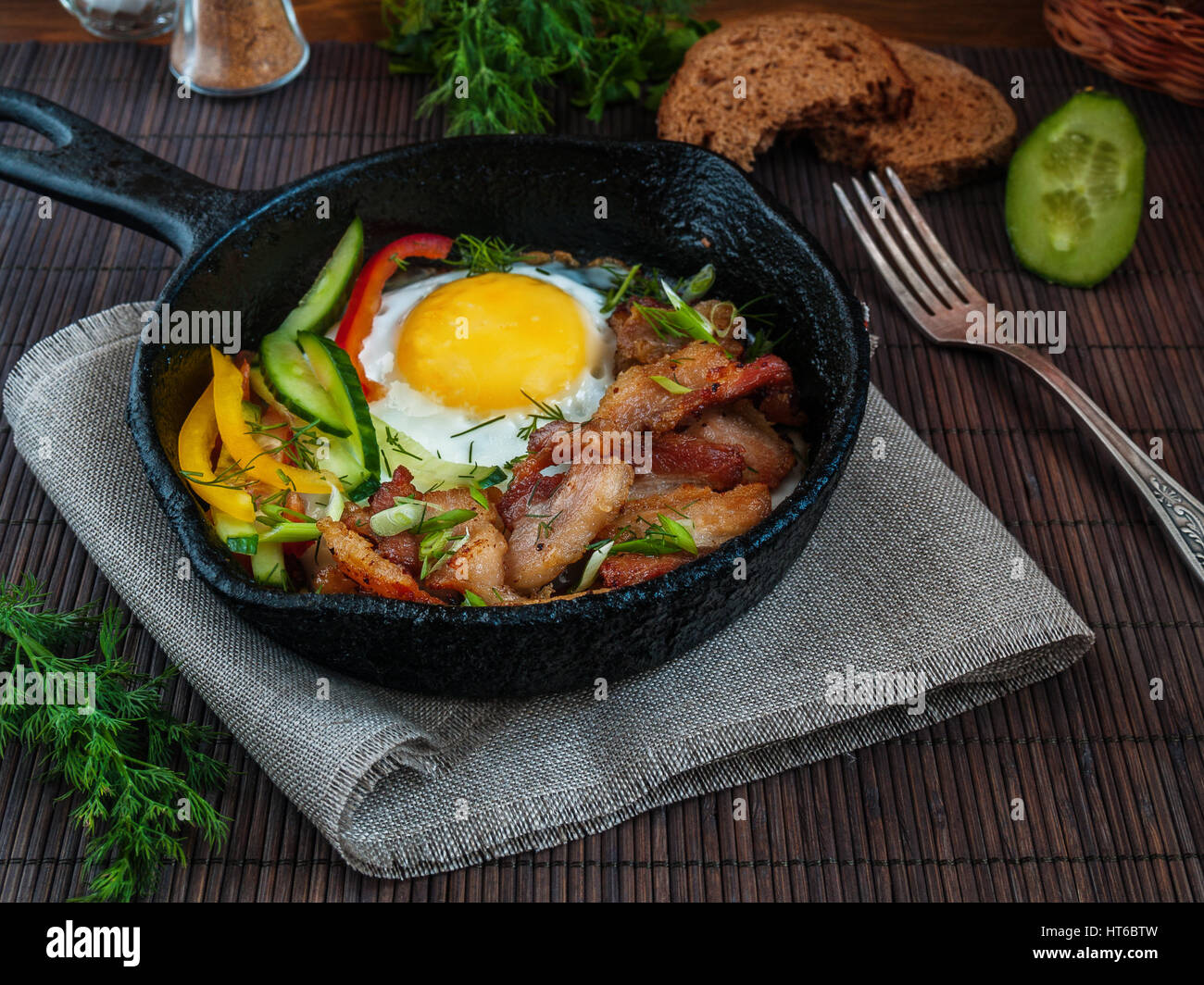 Scrambled eggs with bacon and vegetables custard bread in a pan on the Llano chugonnoy napkin on a table on a bamboo - Stock Image