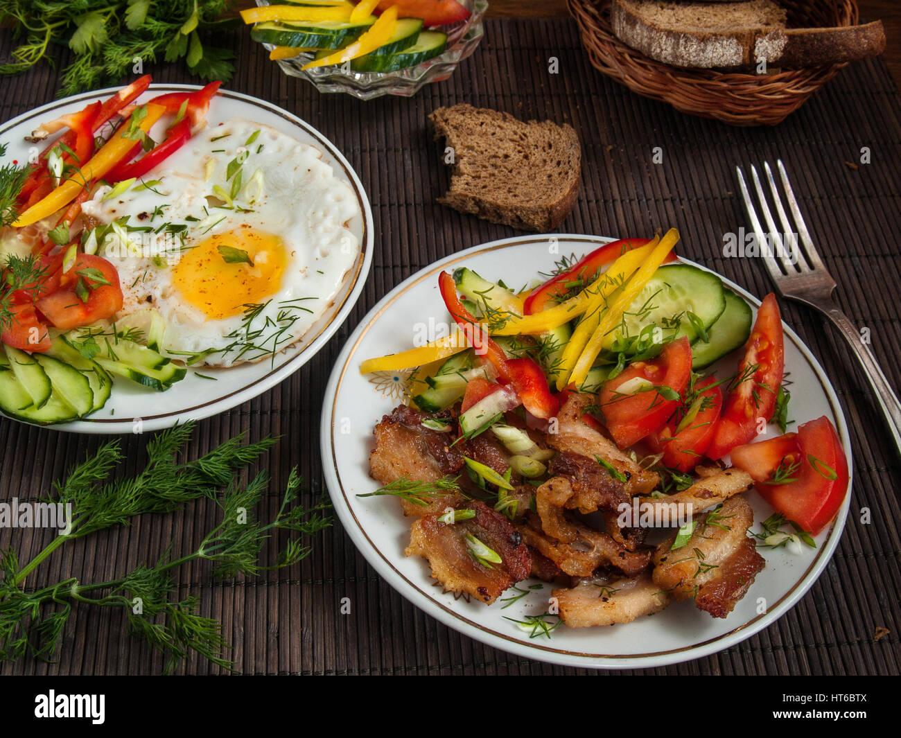 Fried bacon, eggs and vegetables with pepper, tomato and greens on white plates on a table on a bamboo napkin - Stock Image
