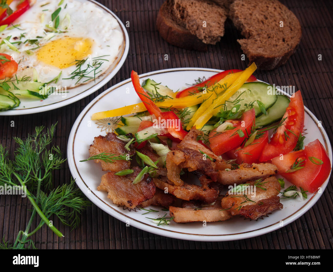 Fried bacon, eggs and vegetables with pepper, tomato and greens on white plates on a table on a bamboo napkin Stock Photo