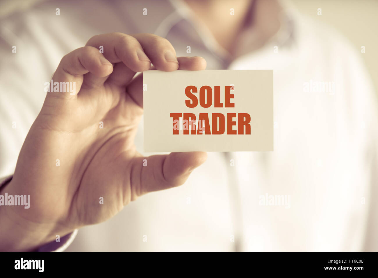 Closeup on businessman holding a card with text SOLE TRADER, business concept image with soft focus background and - Stock Image