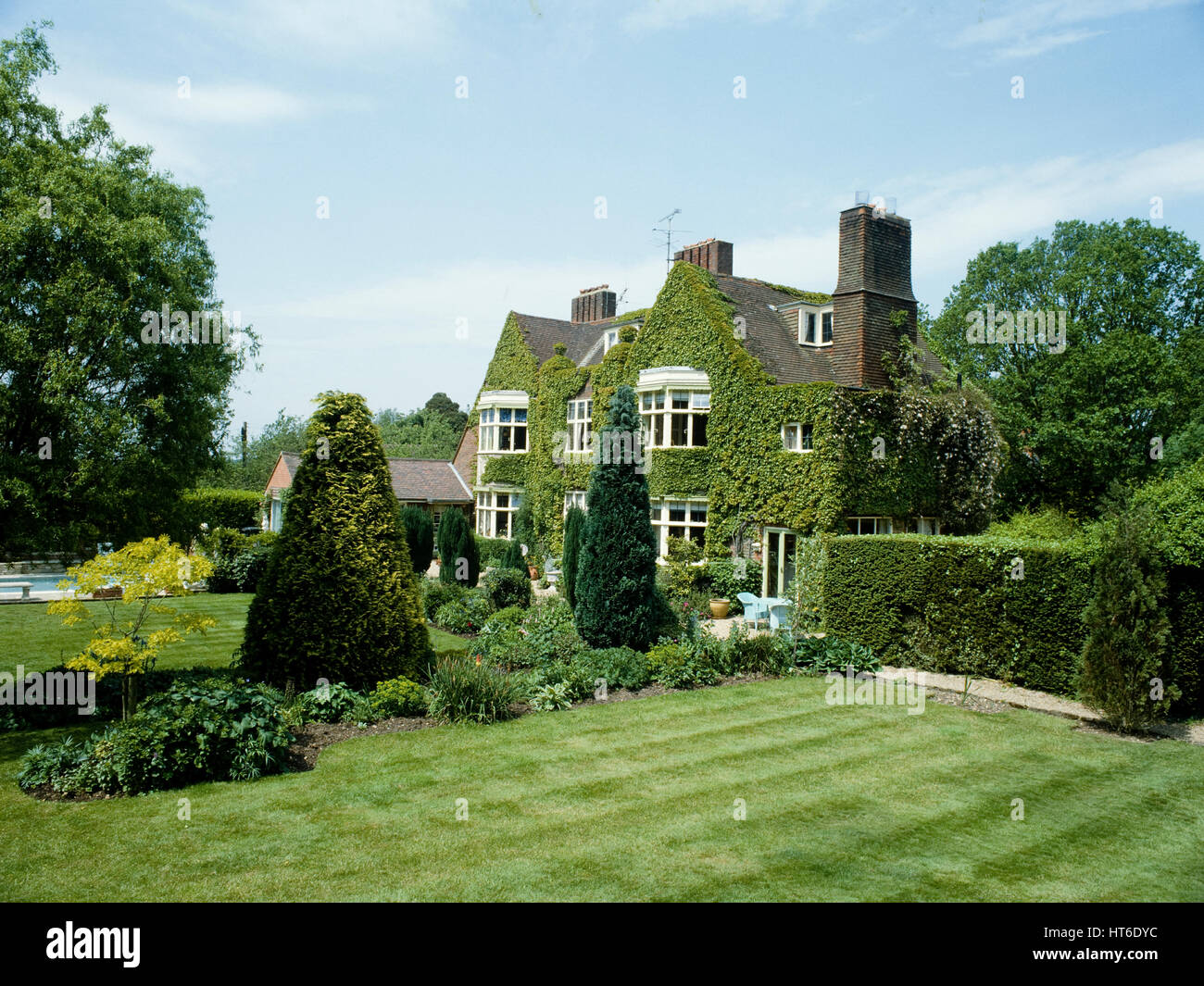 The lawn and exterior of a country house. - Stock Image