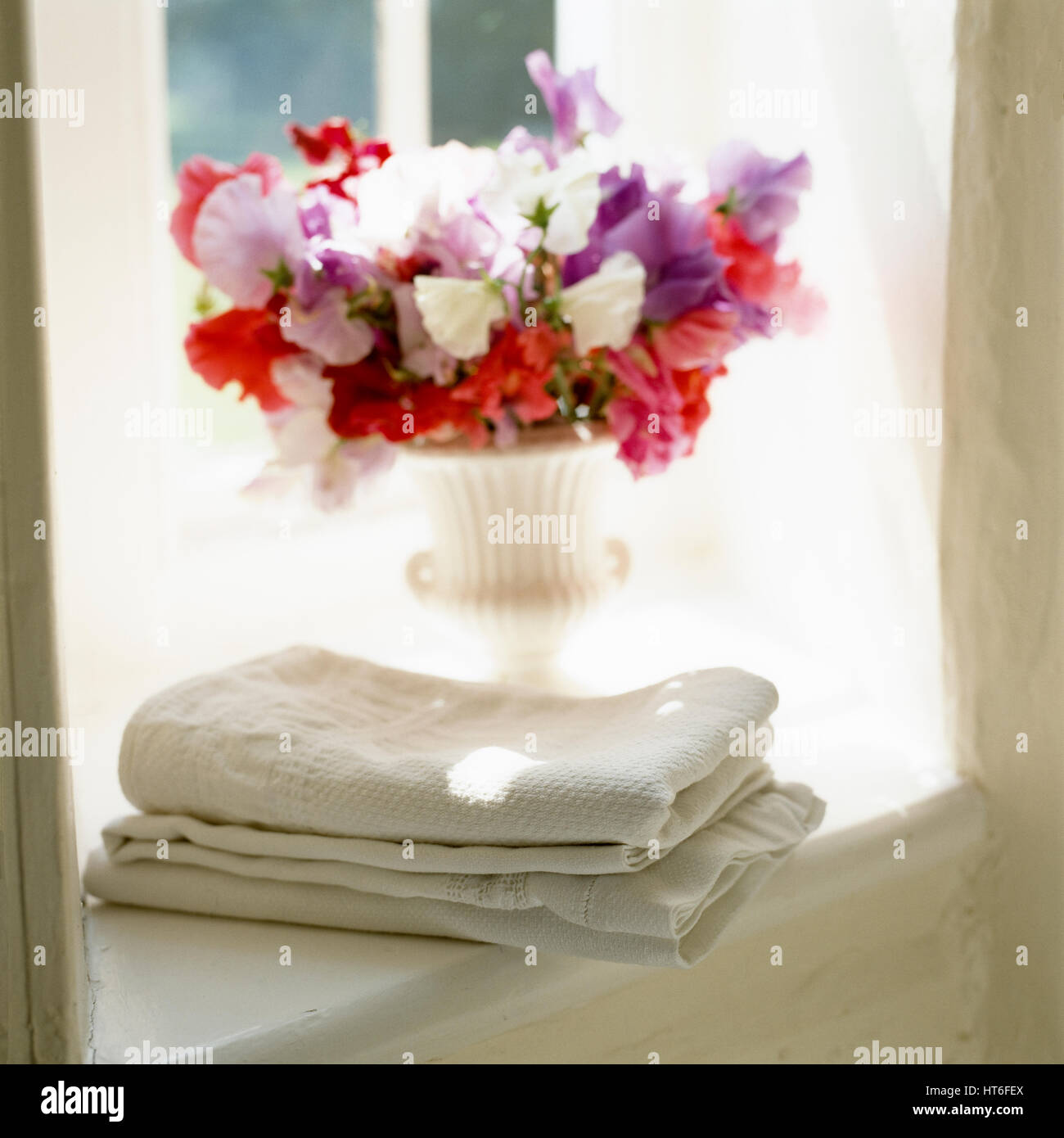 Towels and vase of flowers on windowsill. Stock Photo