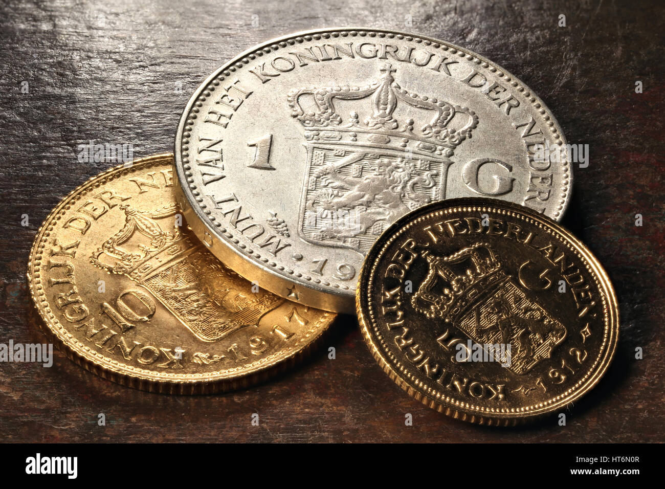 Dutch silver and gold coins on rustic wooden background - Stock Image