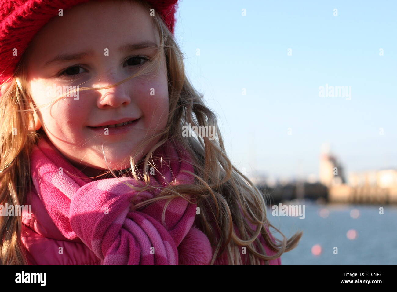Close up picture windswept girl on a windy day, childhood concept, winter concept, cold wind, weather howth ireland, - Stock Image