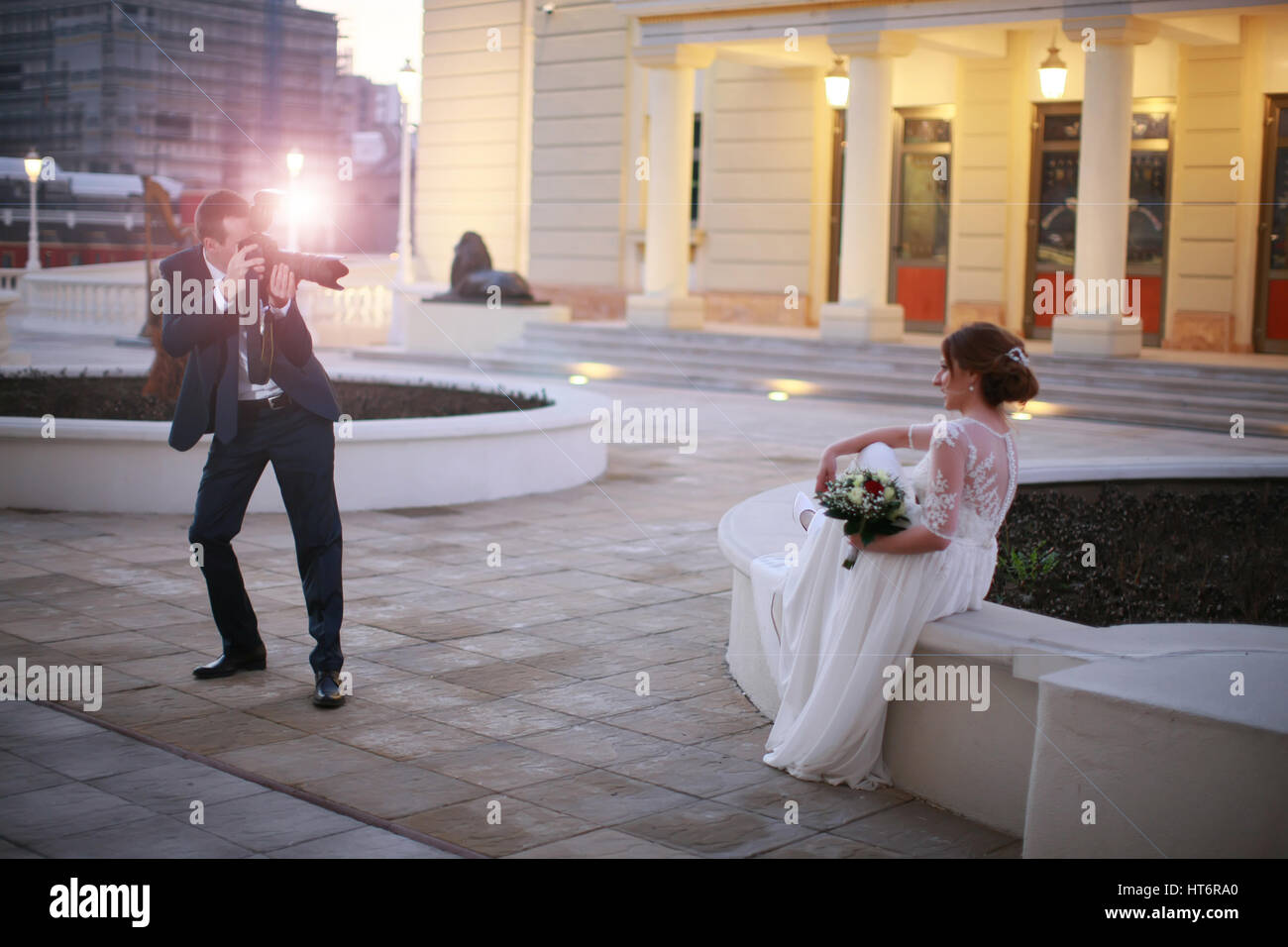 Groom shoot his beautiful bride with digital camera, photo shoot, wedding - Stock Image