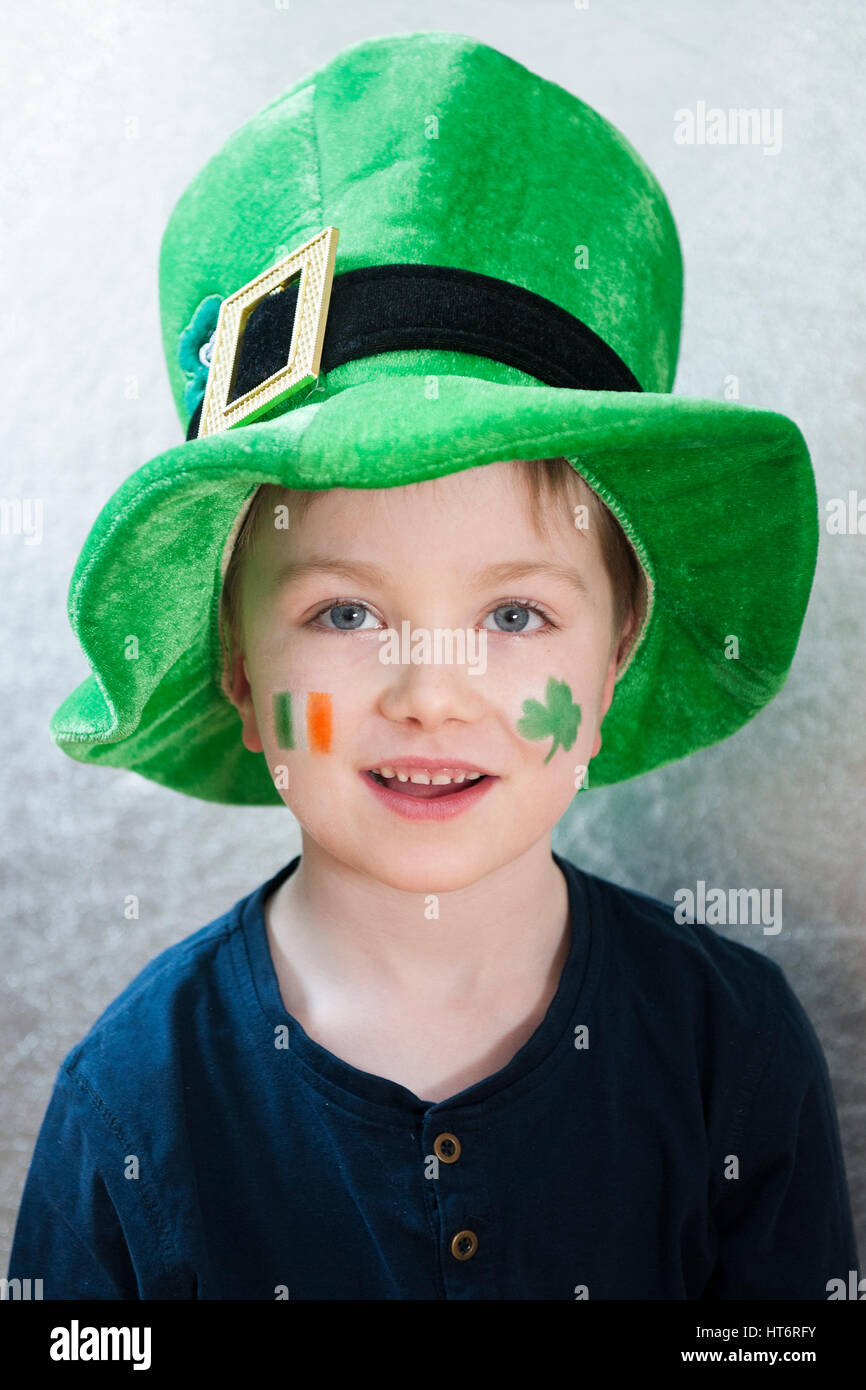 A cute smiling young boy wearing a leprechaun hat and with a face painted Irish tricolor flag and a shamrock for Saint Patricku0027s Day  sc 1 st  Alamy & A cute smiling young boy wearing a leprechaun hat and with a face ...