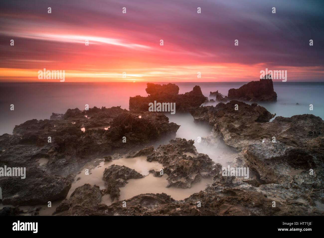 Calm ocean pink sky sunset Stock Photo