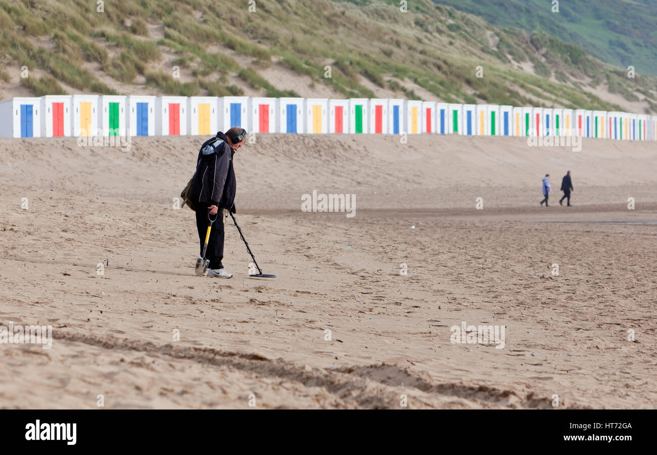 Woolacombe, United Kingdom - May 18, 2011: Man uses a metal detector on Woolacombe beach, with brightly coloured - Stock Image