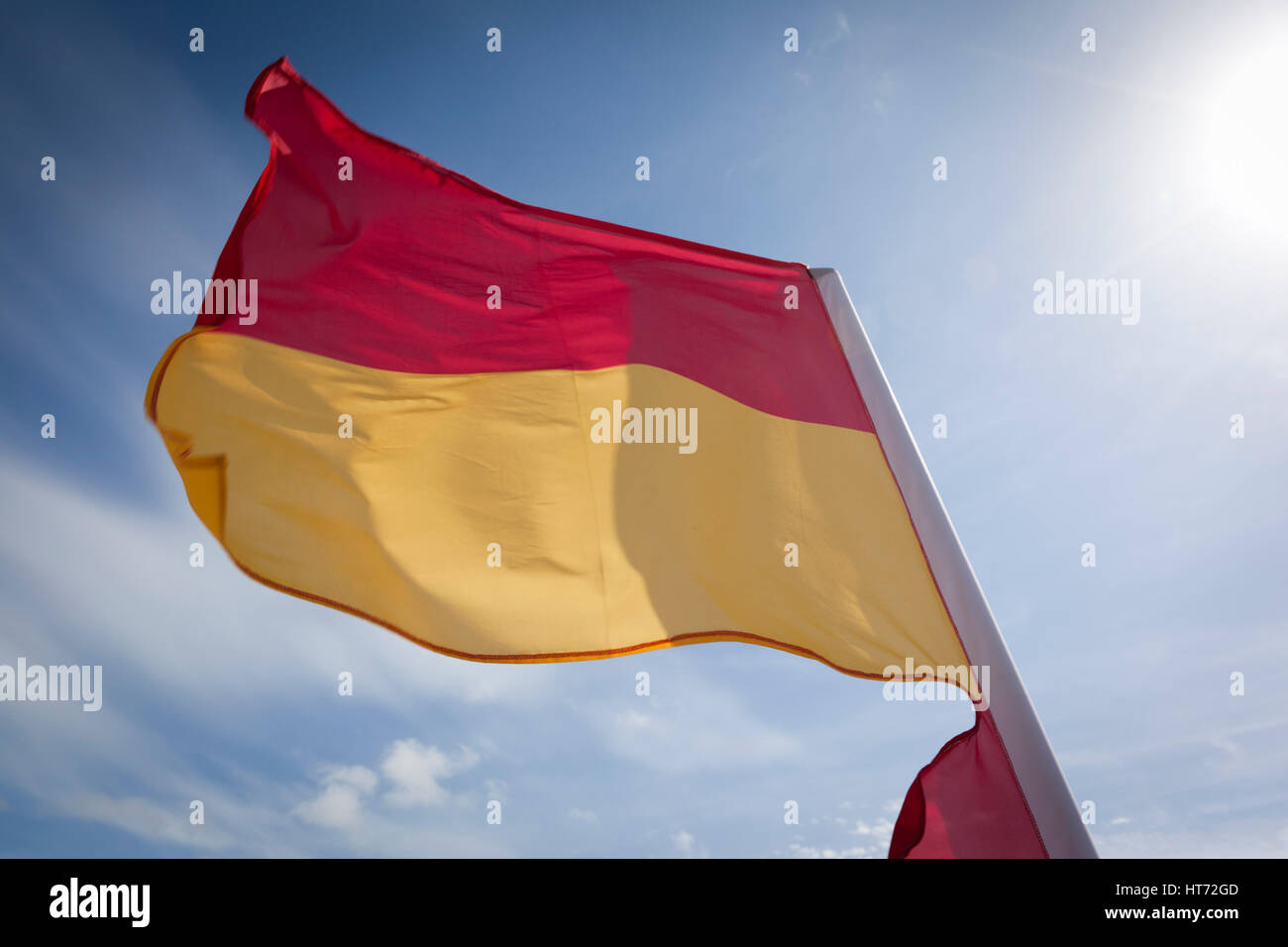 WOOLACOMBE, UK - MAY 19: A red and yellow safety flag fluttering in the wind against a bright blue sky at Woolacombe - Stock Image