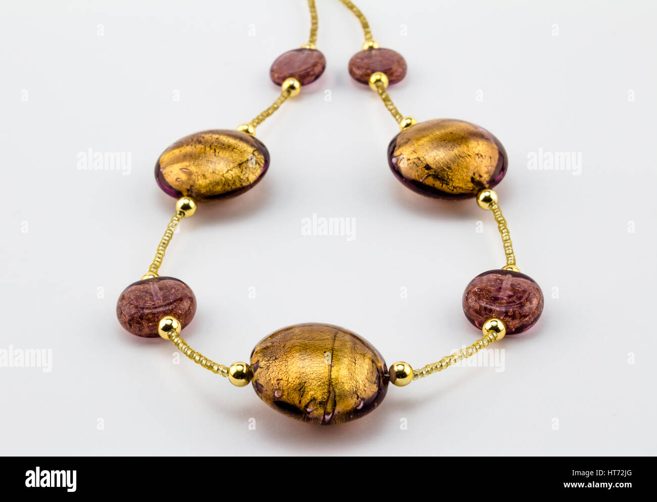 Glass - Murano gold bead and dusty rose necklace close up on white background - Venice - Stock Image