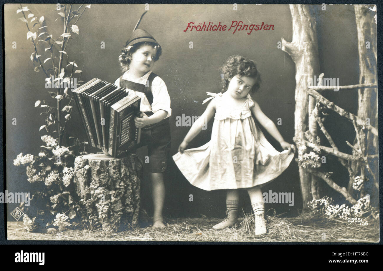 GERMANY - CIRCA 1914: A postcard printed in Germany, shows a boy and a girl. The inscription in German: Happy Pentecost, - Stock Image
