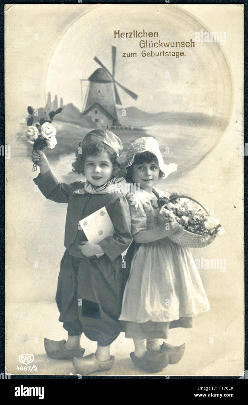 A greeting postcard printed in Germany, shows a boy and a girl with flowers  in