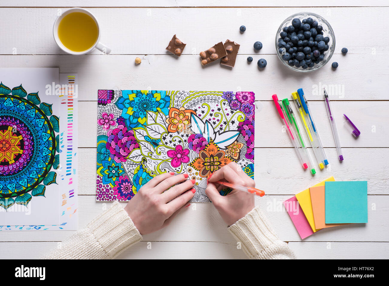 Flat lay, female colouring adult colouring books, new stress relieving trend - Stock Image
