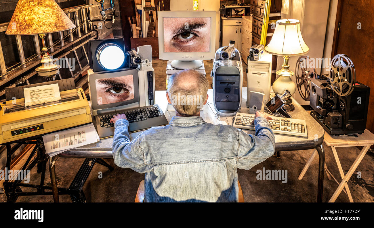A paranoid man sits and watches his computers as his computers watch him. - Stock Image