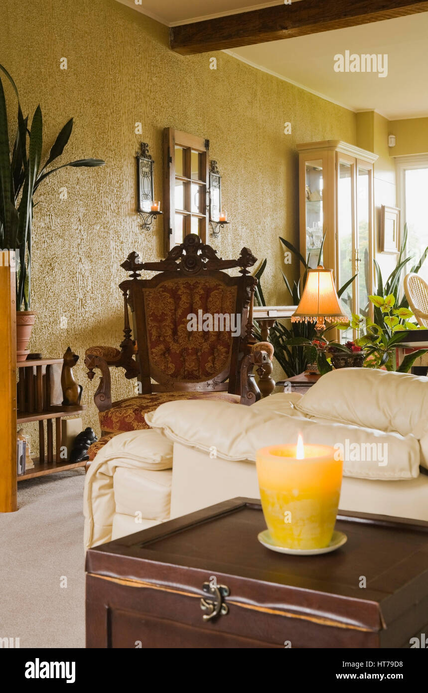 Living room with cream colored leather sofa and upholstered antique armchair in old house inetrior. - Stock Image