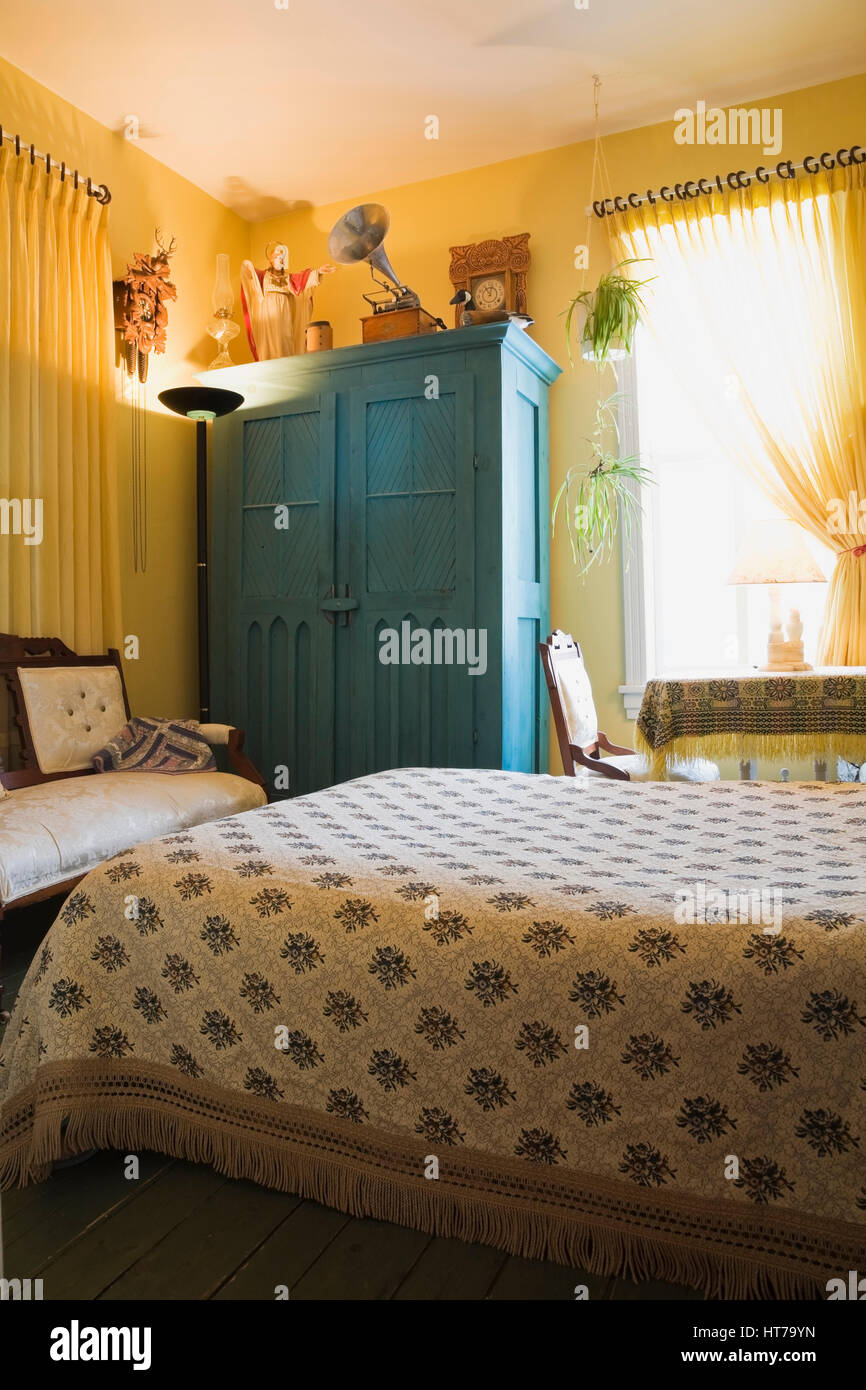 Master bedroom with floral bedspread and wooden armoire in 1904 Victorian old house interior. - Stock Image