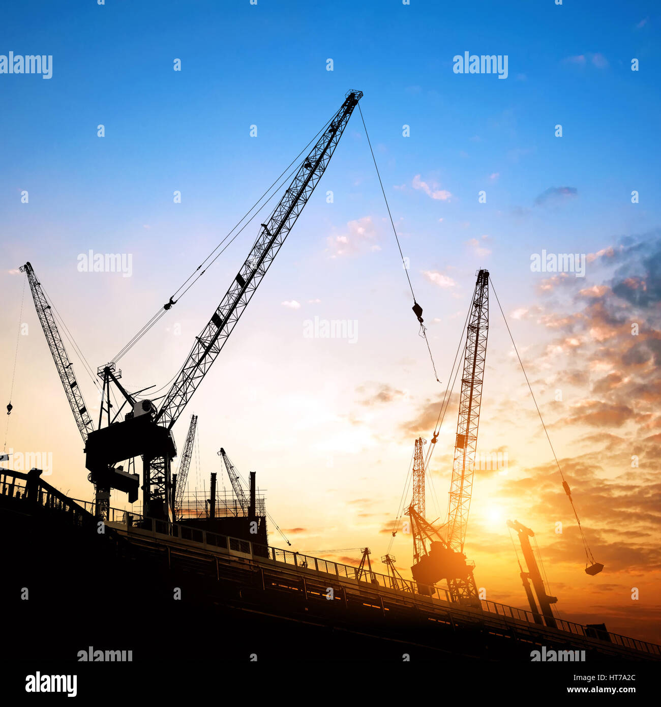 Construction site, cranes and scaffolding silhouette. - Stock Image