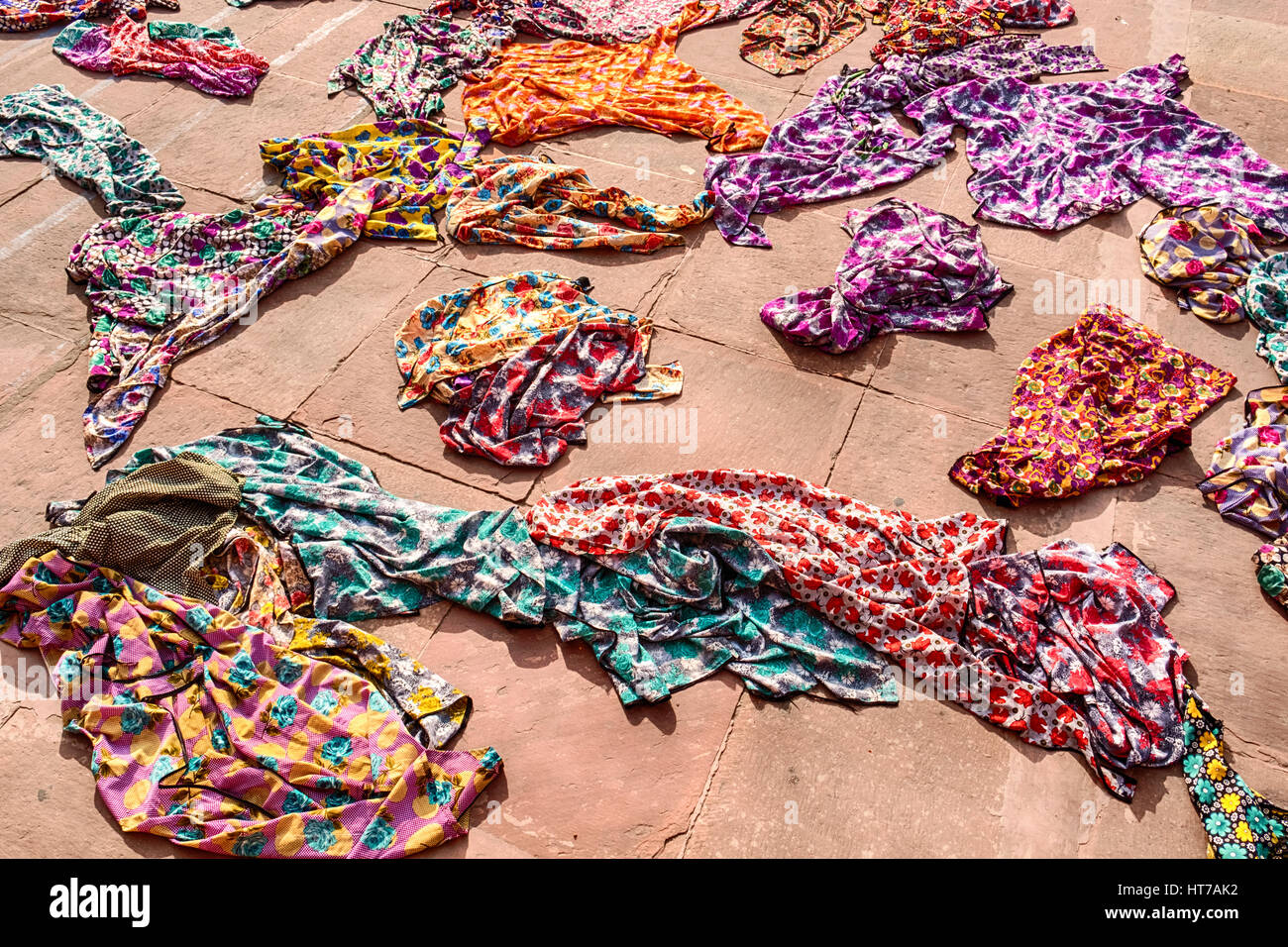 A pile of colorful hijabs, or head coverings, for use by tourists are scattered on the ground by the entrance of - Stock Image