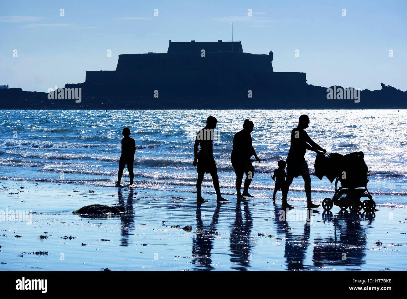 Silhouettes of a family at St. Malo beach walking along the sea at dusk. In the background the contours of Fort - Stock Image