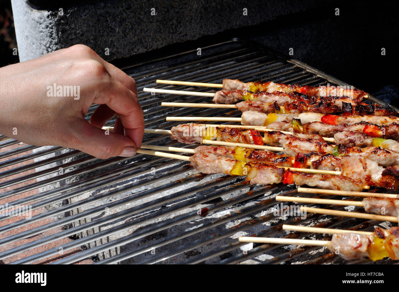 Hand with Meat and Vegetable on Barbecue - Stock Image