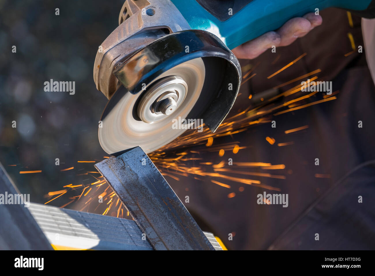 An angle grinder cutting through steel and giving off sparks - Stock Image