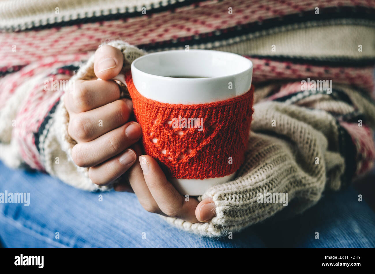 Red Knitted woolen cup with heart pattern in female hands. Hands ...