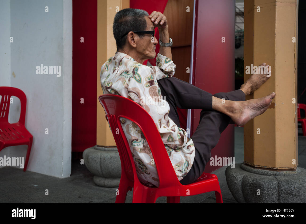 18.01.2017, Singapore, Republic of Singapore, Asia - A man relaxes on a plastic chair in Singapore's Chinatown district. Stock Photo