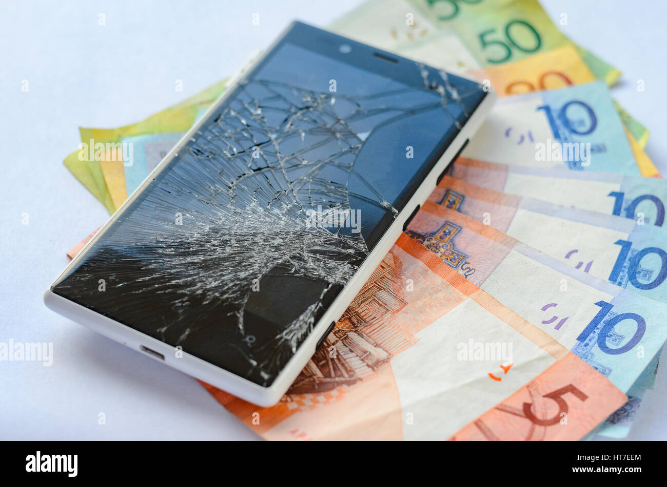 Broken smartphone lying on money banknotes on a White background. Losing money concept Stock Photo
